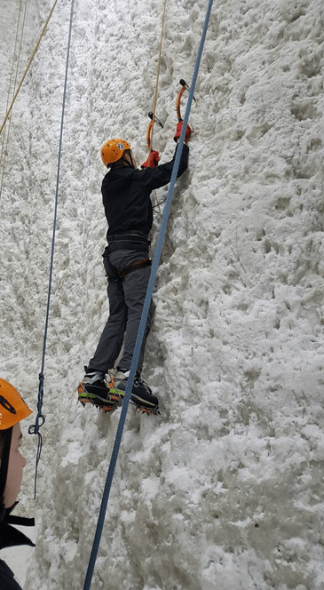 An Explorer scales an ice wall